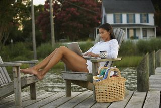Woman.dock.laptop.Ariel.Skelley.BlendImages.Corbis